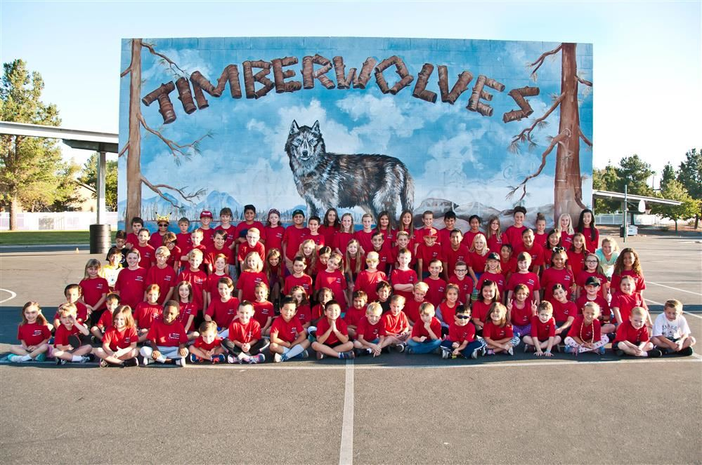 Running club students in front of ARES timberwolf wall