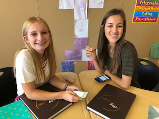 Two female students sitting at their desks smiling for the camera.
